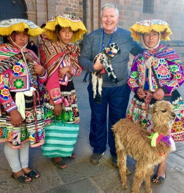 Wayne parties with the locals in Cuzco as he carries a lamb.