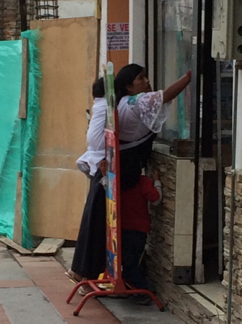 Cotacachi, Ecuador - Woman with children cleans windows in store