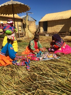 Women outside their homes on the floating island sharing foods to be prepared for family meals